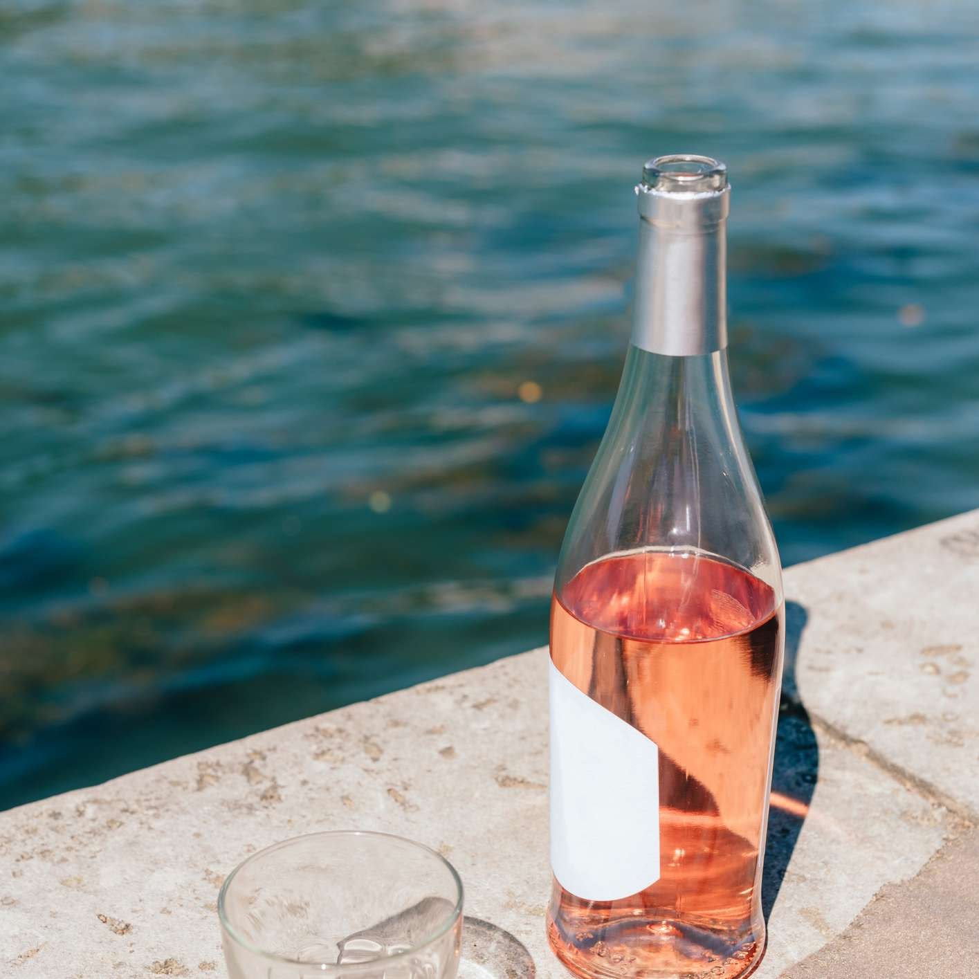 Bottle of rosé with a glass on pool ledge.