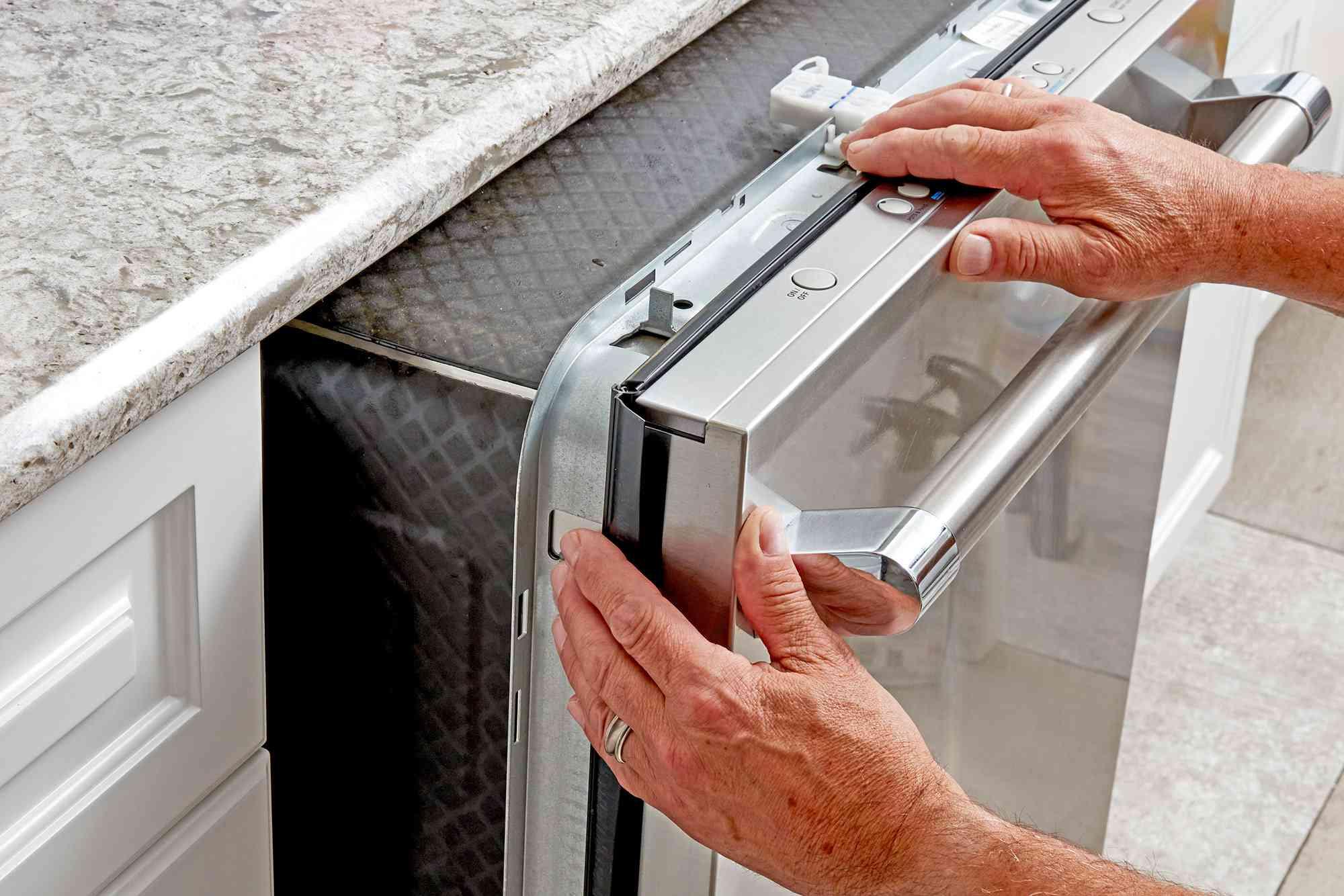 New dishwasher sliding into kitchen opening