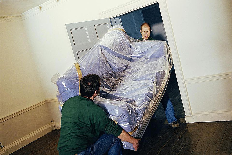 Two men moving a couch that's wrapped in plastic
