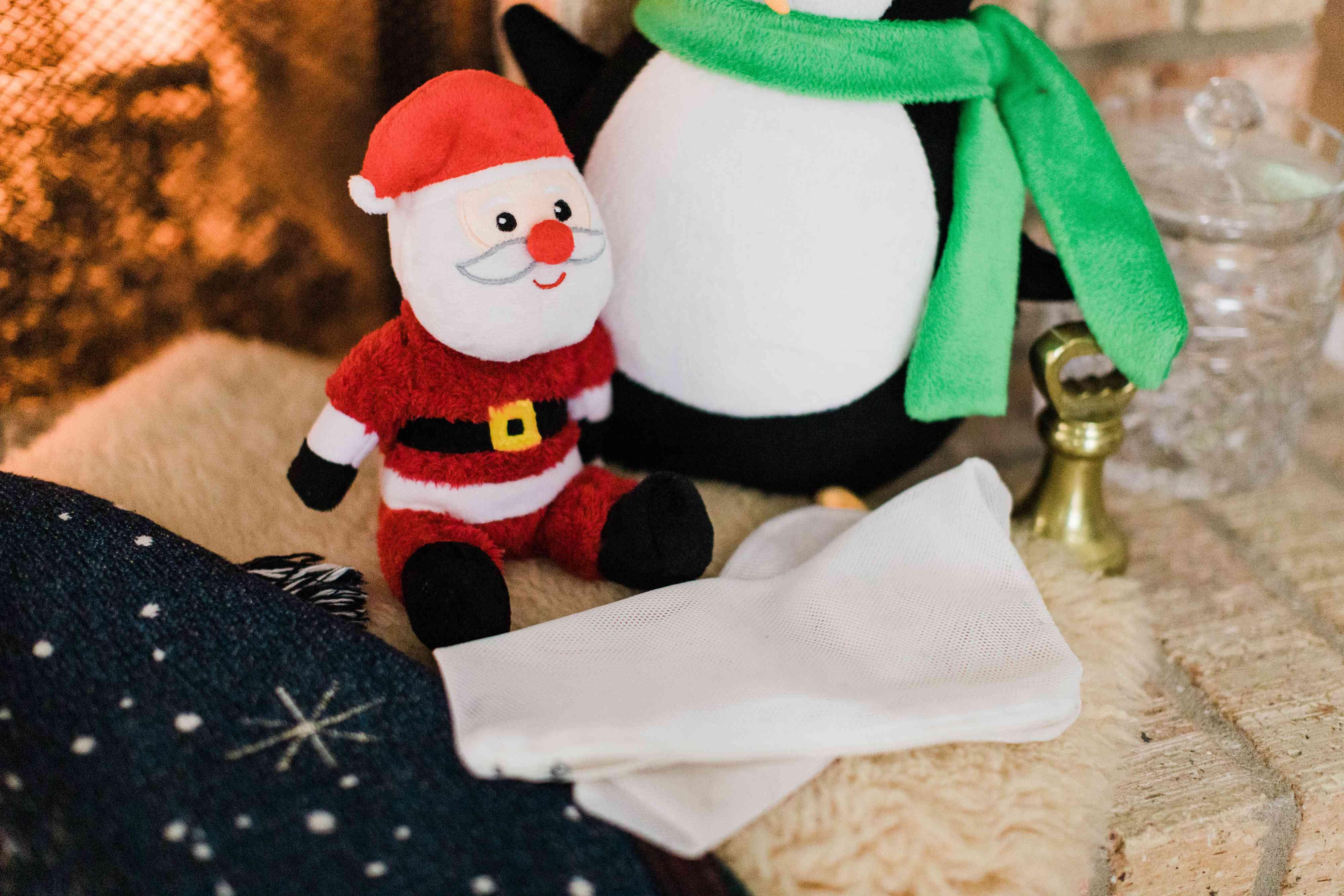Holiday plush toys behind a folded mesh laundry bag