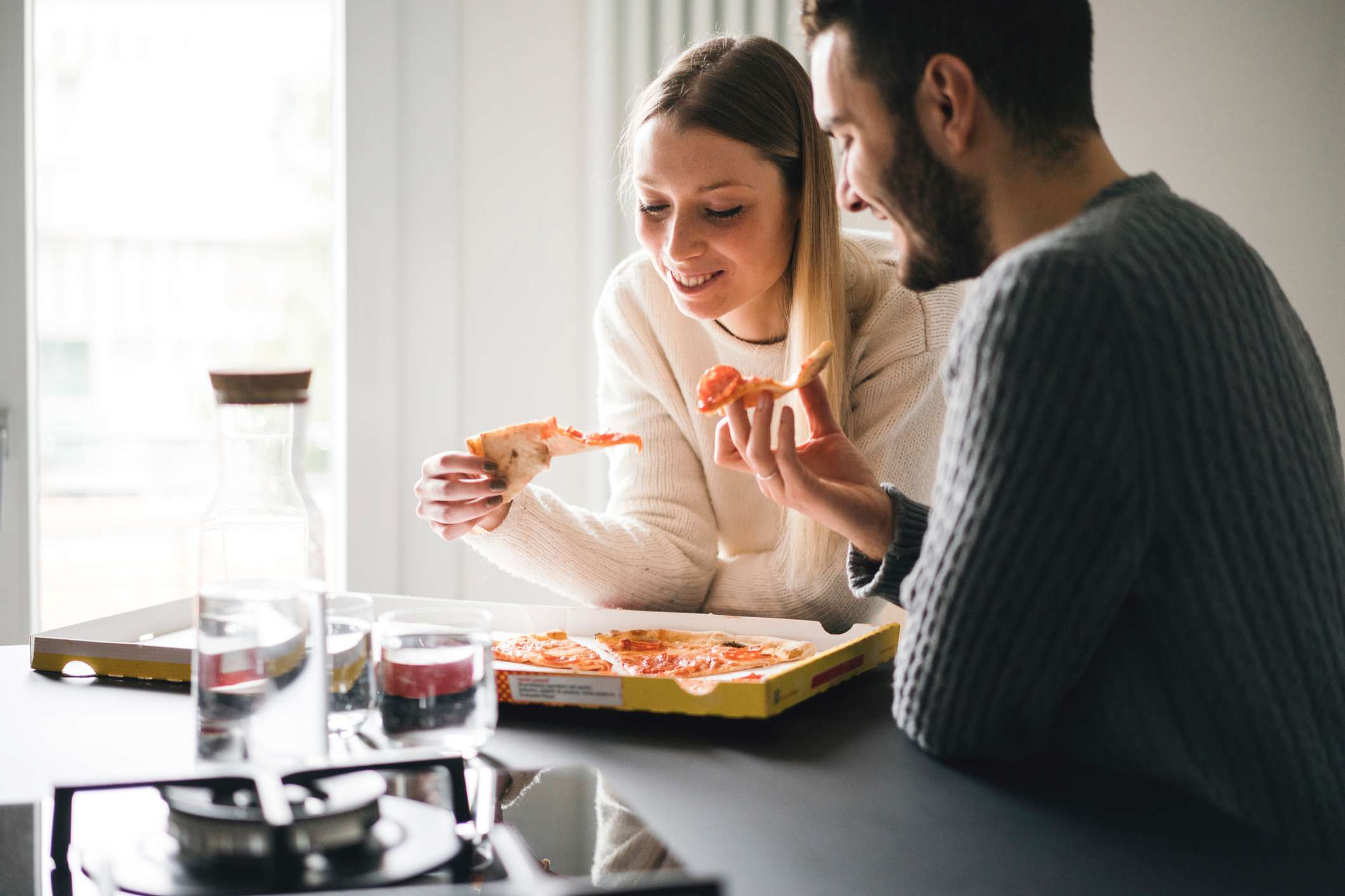 A couple eating pizza in the kitchen.