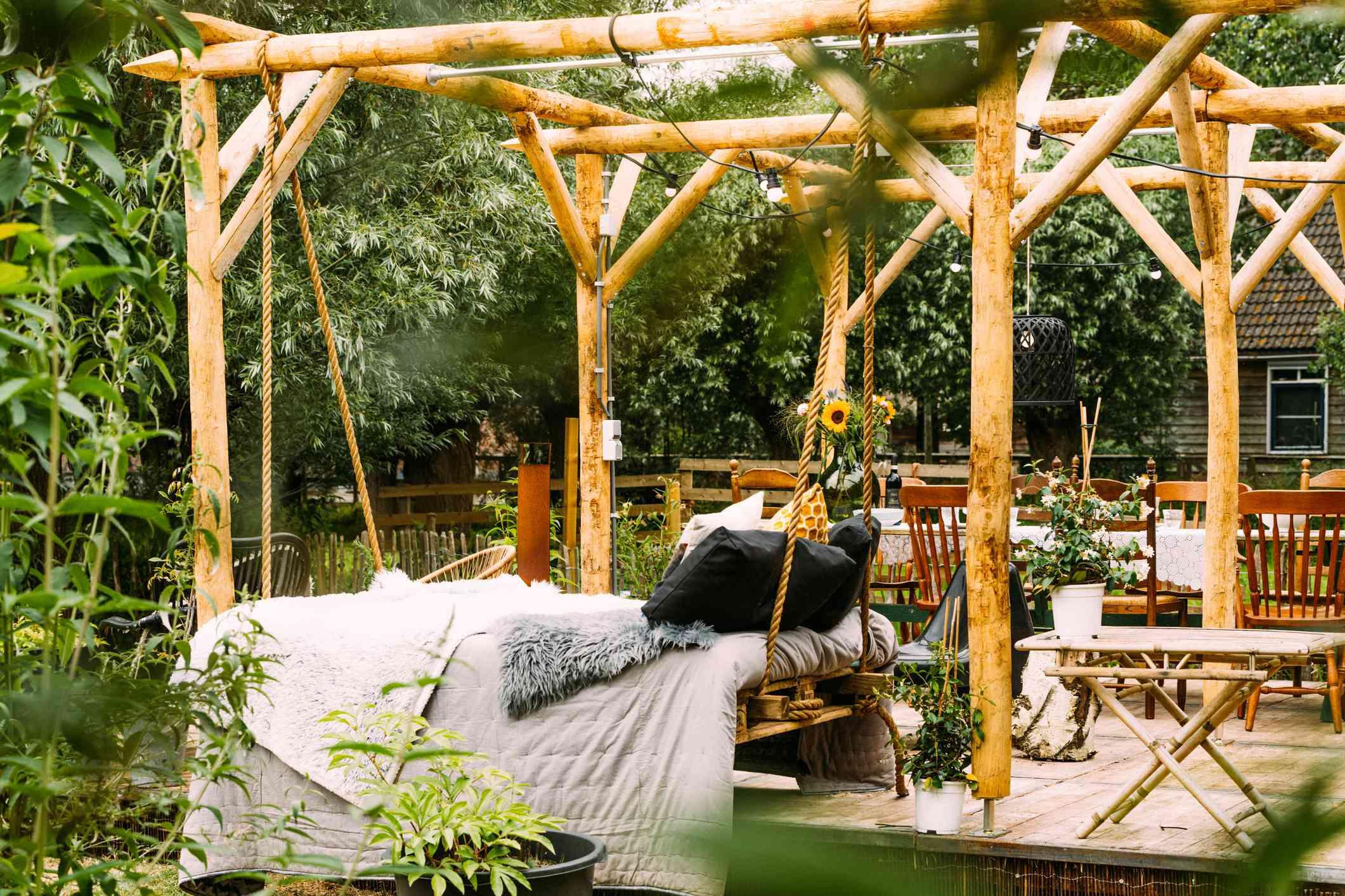 Patio de jardín de madera con árboles verdes en un entorno de verano y un diván