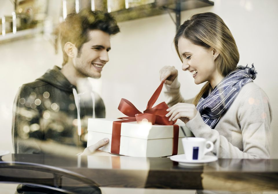 Woman unwraps gift from man