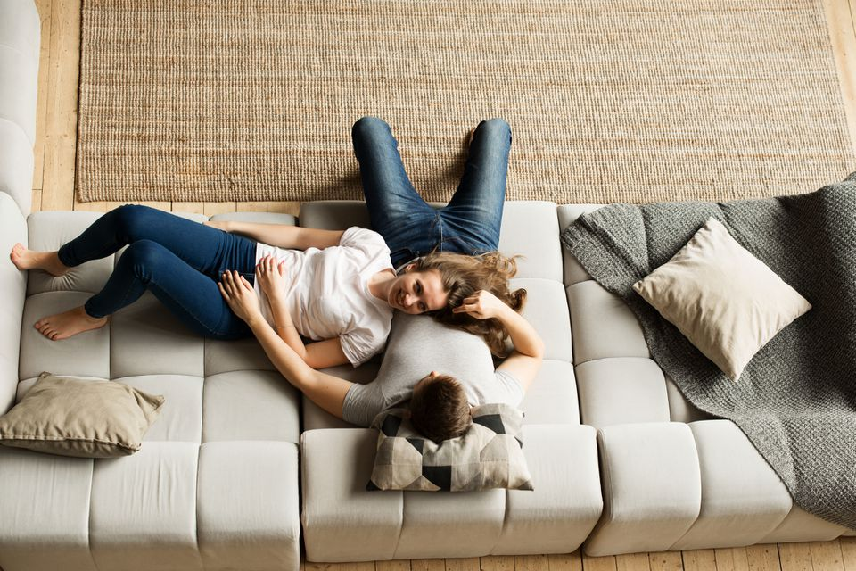 couple cozying up on a big sofa