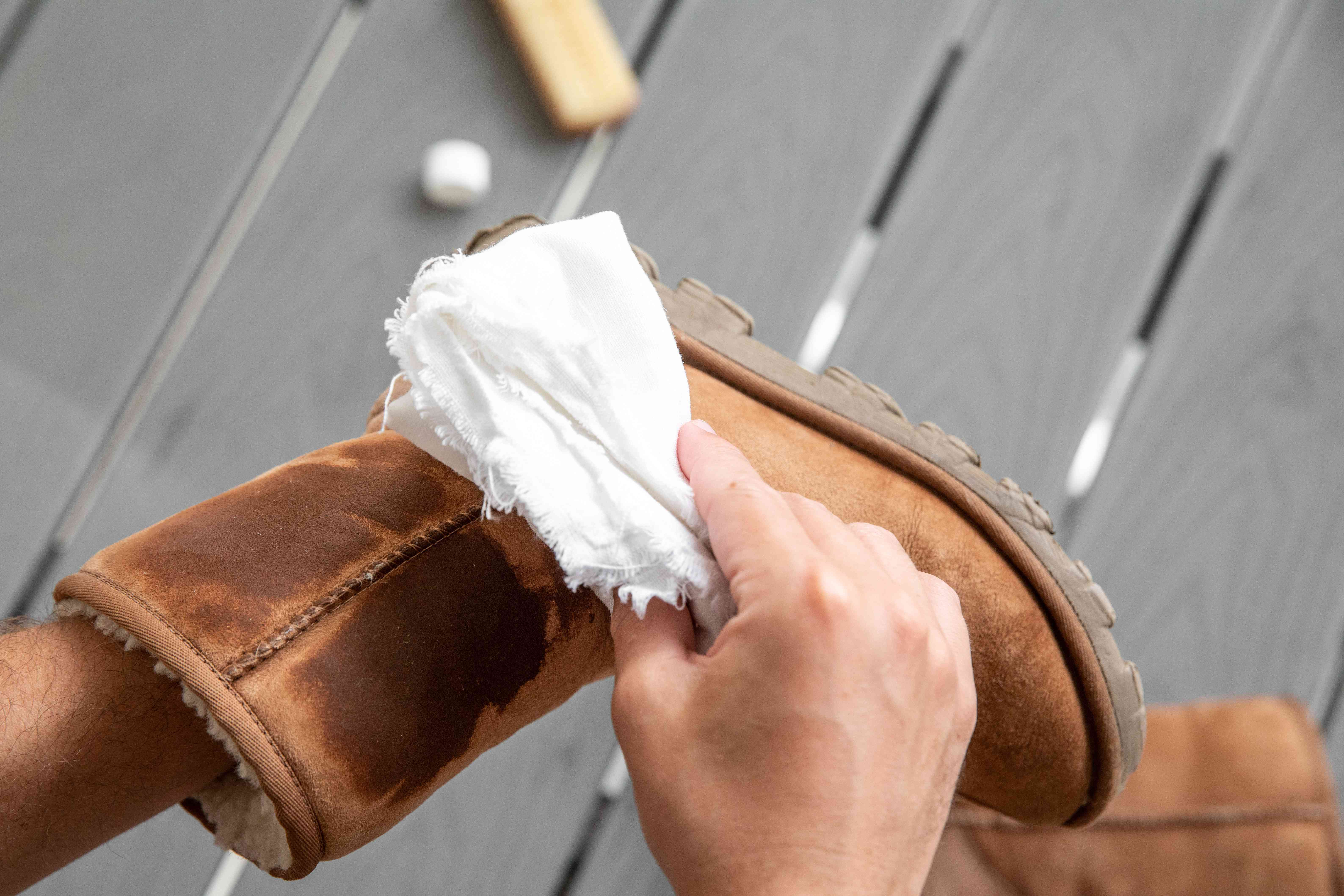 Someone wiping down Ugg boots with a damp cloth