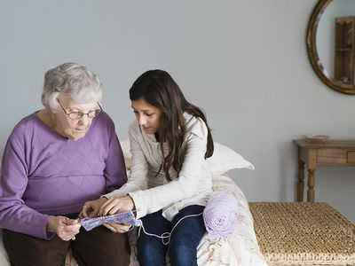 Grandmother and granddaughter knitting together