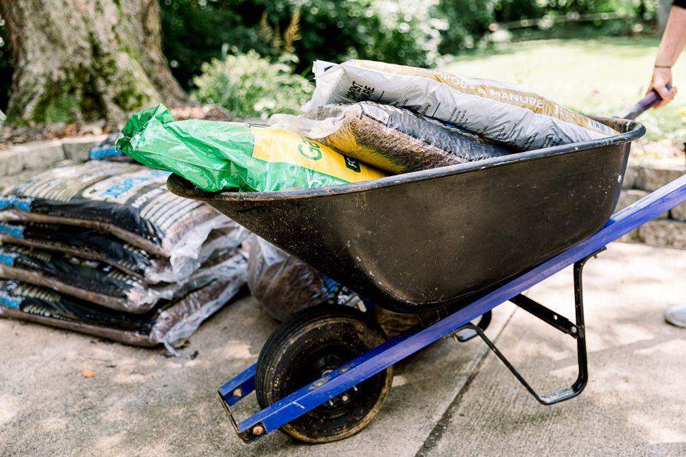 Using a wheelbarrow to haul compost, soil, and mulch