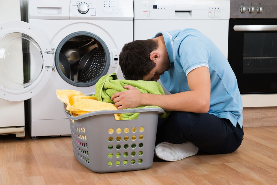 Frustrated man sitting in front of washing machine with laundry basket.