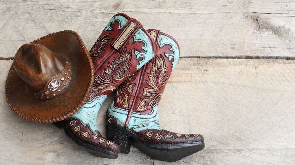 Cowboy boots and hat laying on a wood background