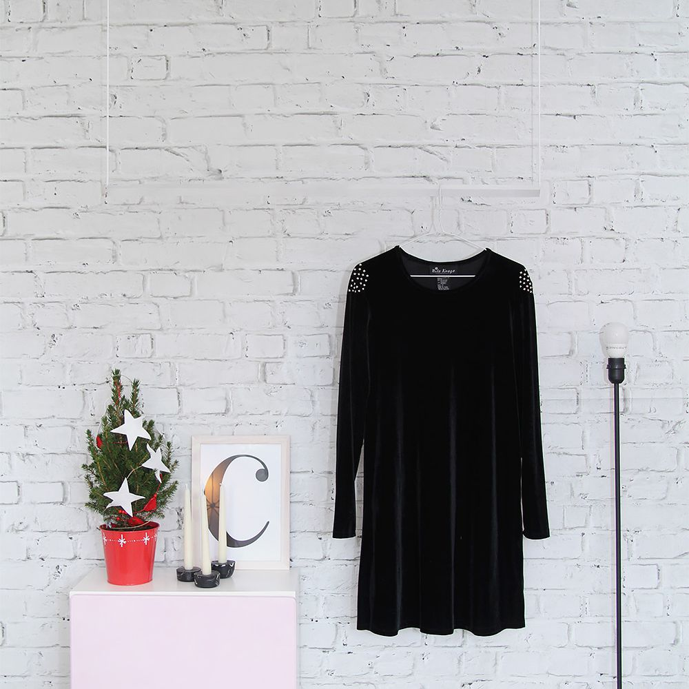 fake white brick wall with a dress hanging on it