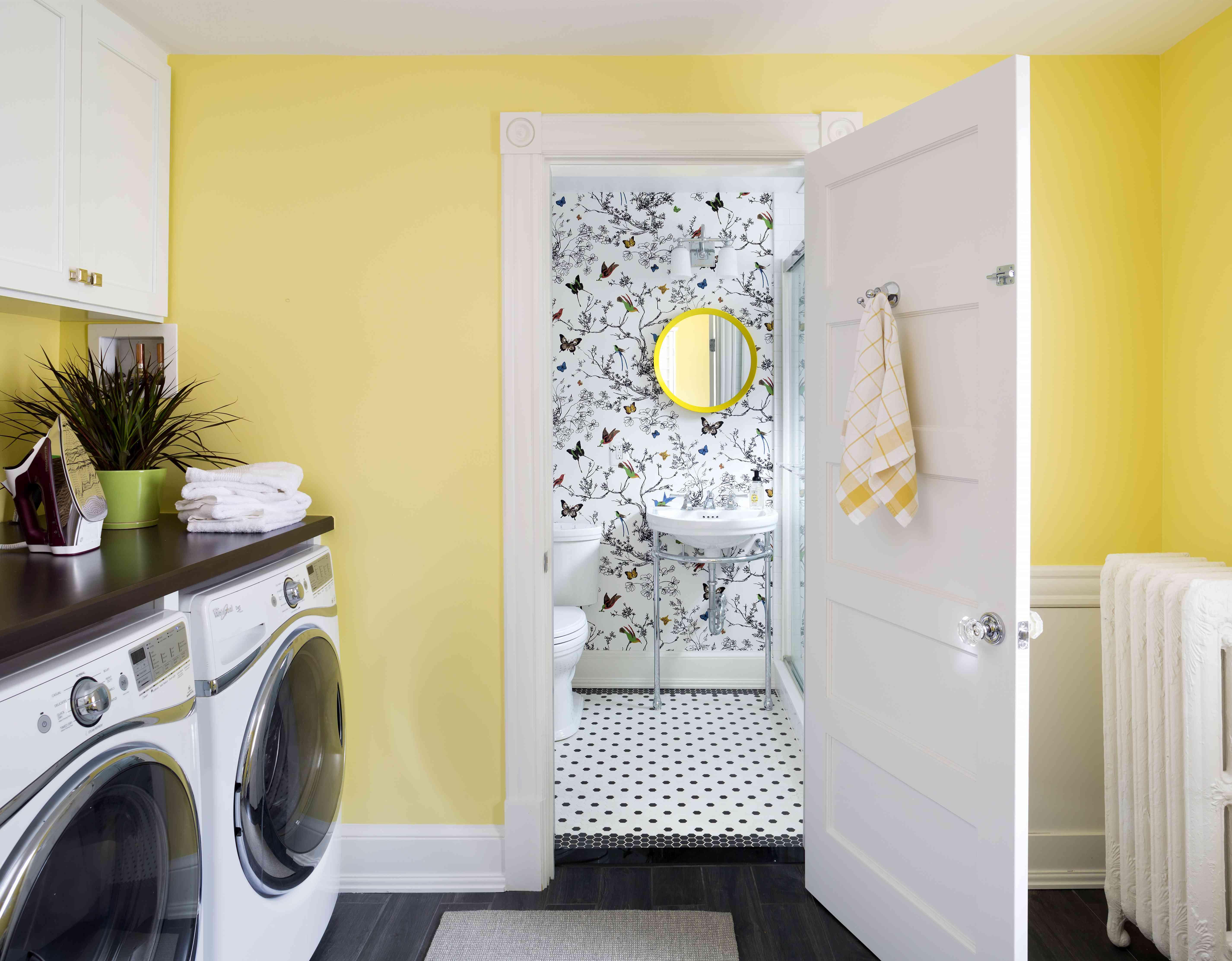 Cuarto de lavado con puerta abierta a un baño con papel tapiz