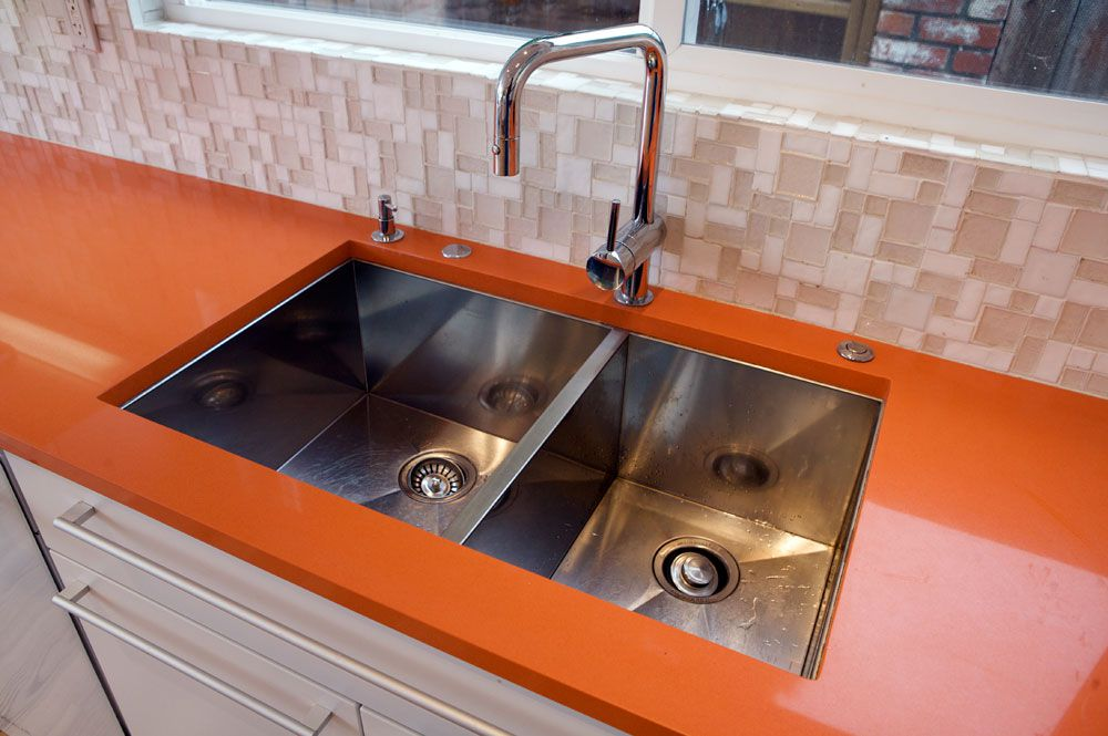 Orange quartz kitchen countertop with sink.