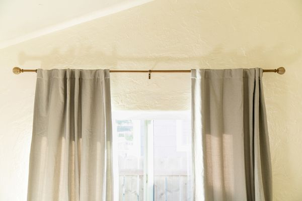 Tan drapes hanging from each end of curtain rod above window