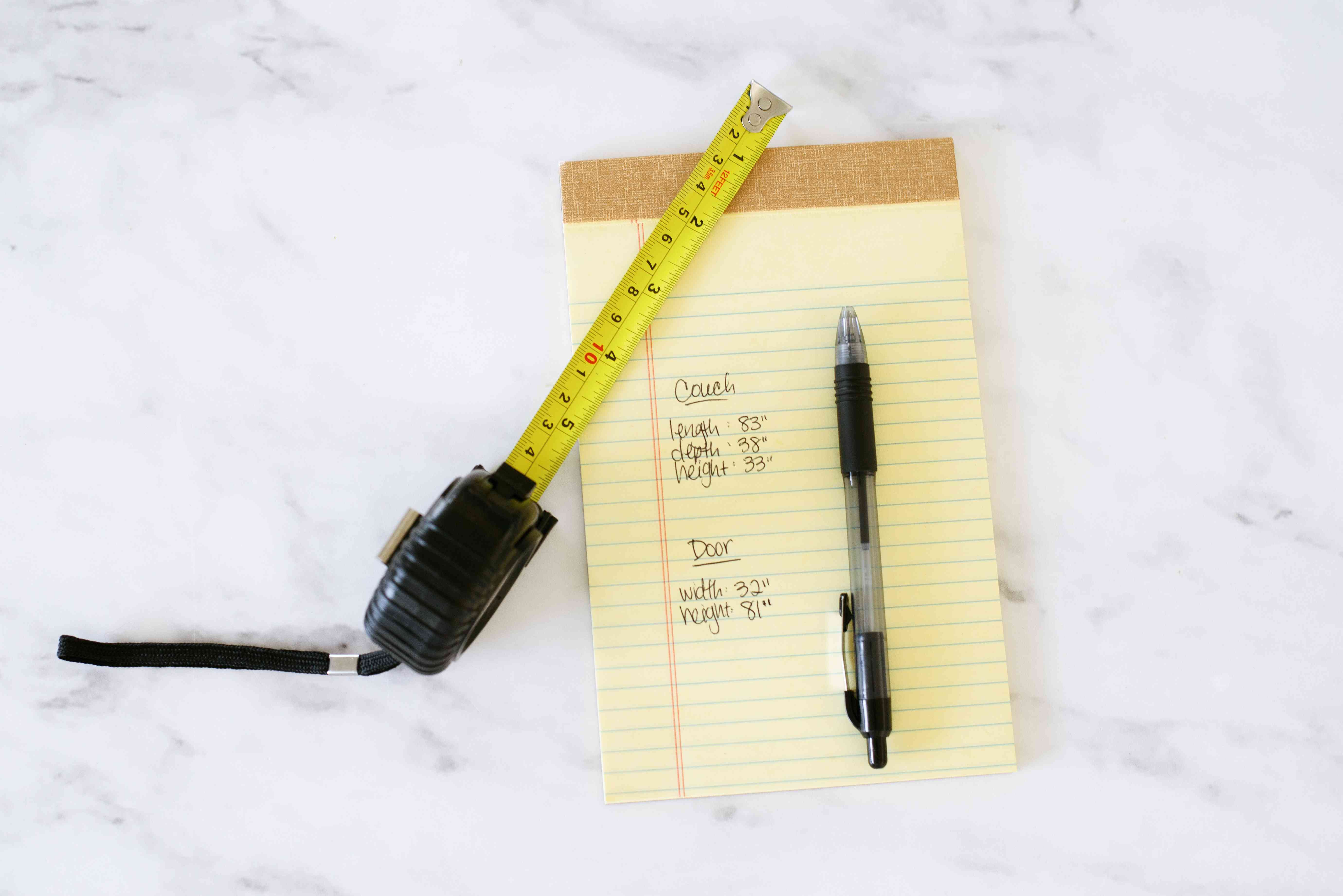 Measurements written on yellow notepad with pen and measuring tape