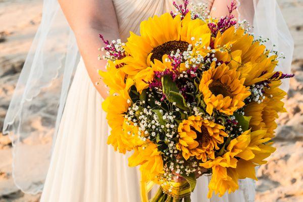 Bride on beach with sunflower bouquet