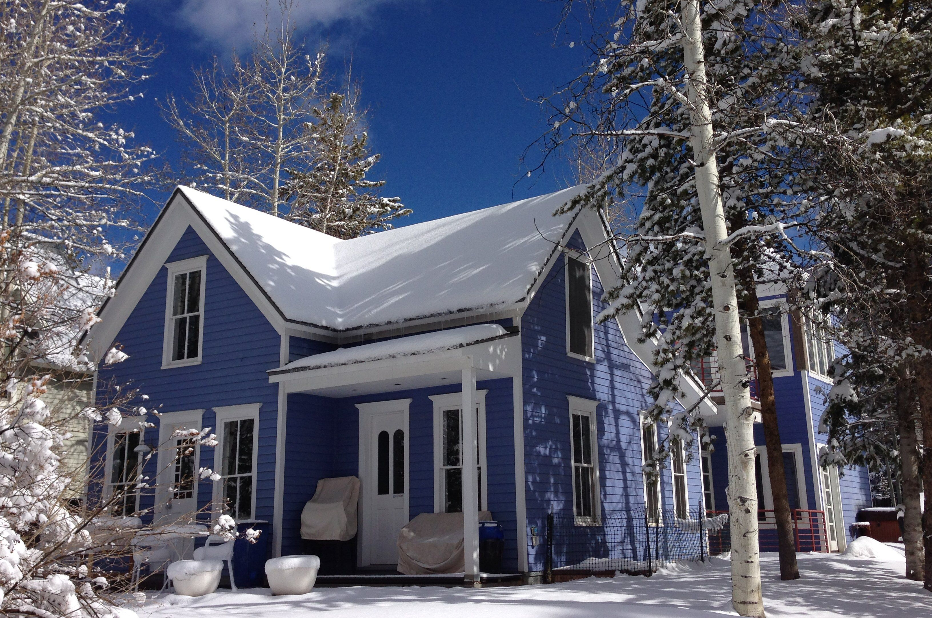 Large blue farmhouse in winter