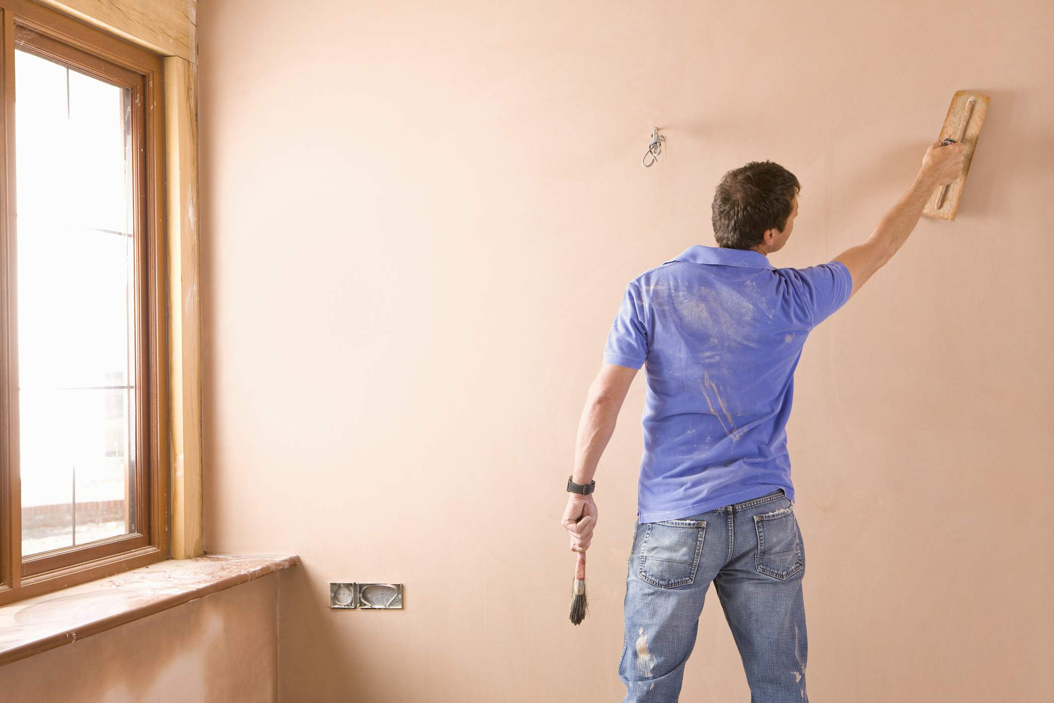 Man applying second coat of plaster to wall