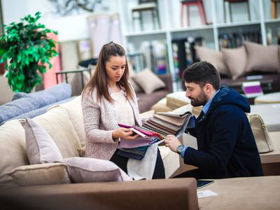 Couple choosing fabric for furniture at furniture store
