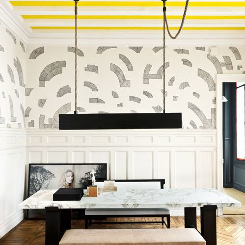 Stylish, modern dining room with ceiling painted in yellow stripes