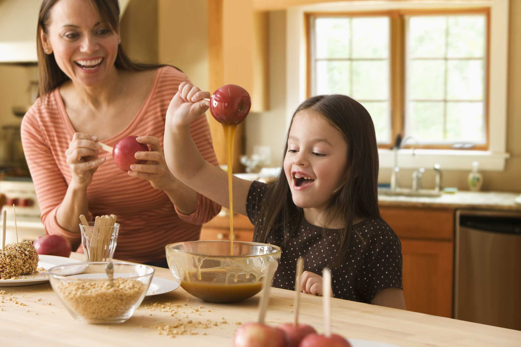 Mom and child making caramel apples