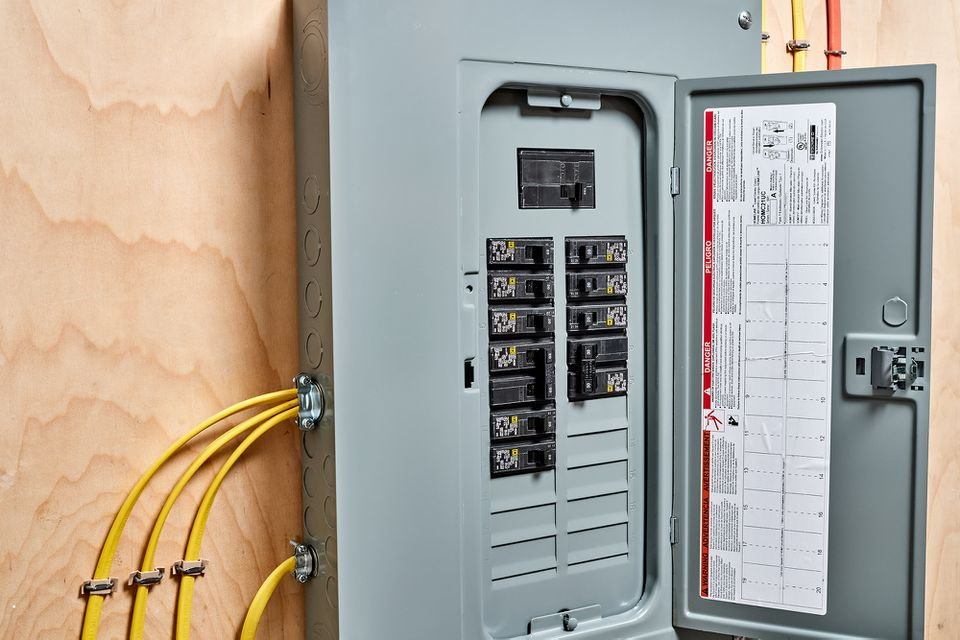 Main electrical service utility box with door open and yellow wires coming from sides