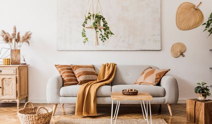 The stylish boho compostion at living room interior with design gray sofa, wooden coffee table, commode and elegant personal accessories. Honey yellow pillow and plaid. Cozy apartment. Home decor