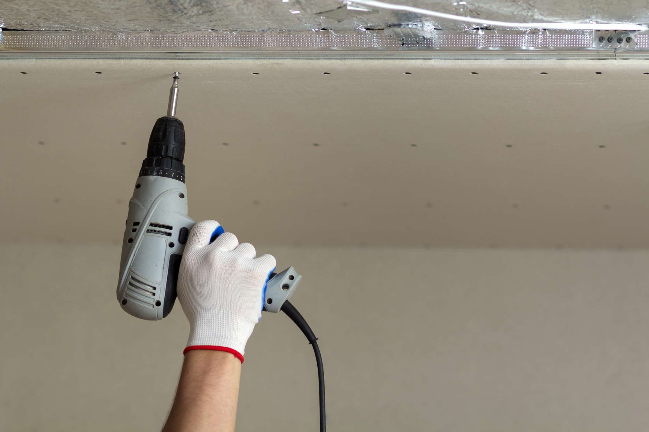 Construction working using screwdriver on ceiling drywall