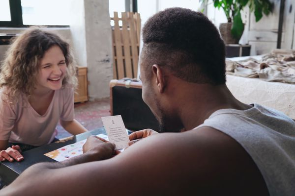 Happy couple in pajamas playing the board game on the floor. Man throws dice and puts the card, woman laugh