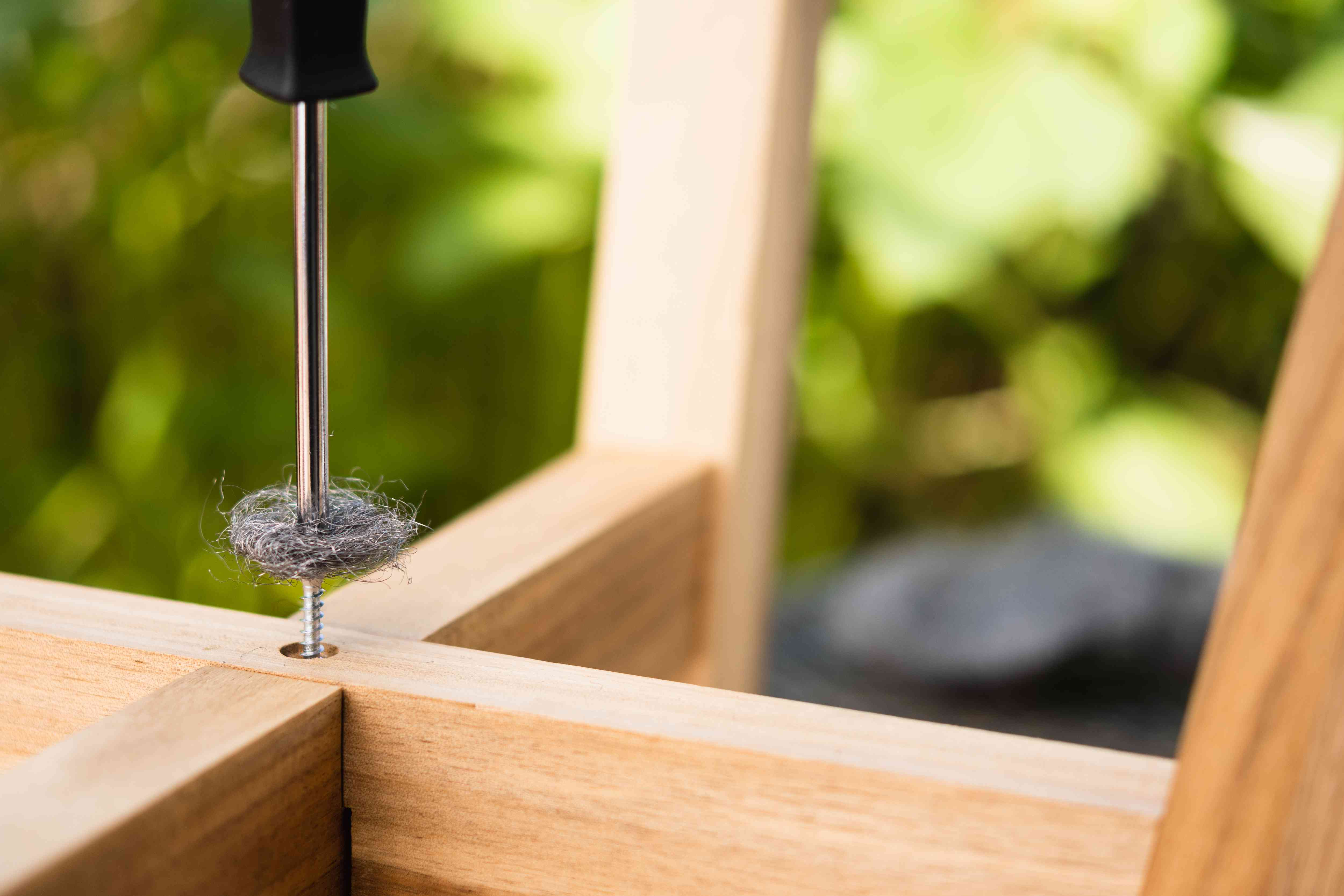 Steel wool inserted between stripped screw head and drill bit in wooden fixture