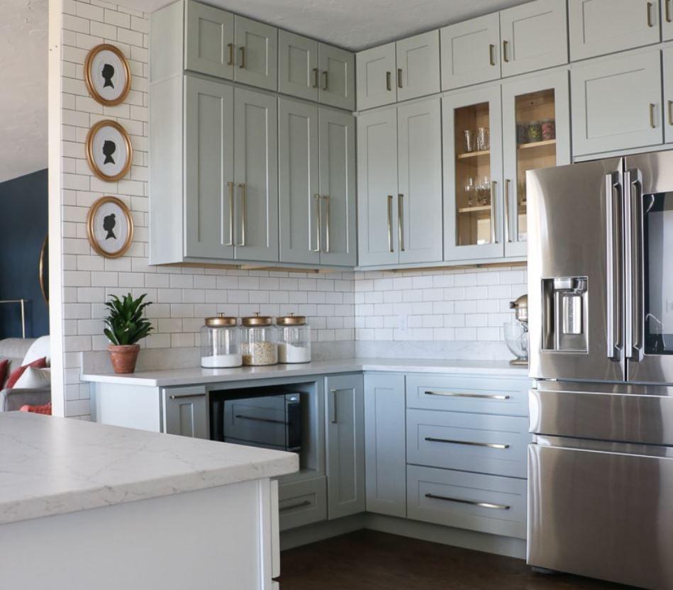 Cocina actualizada con gabinetes de color azul claro. y paredes de azulejos del metro.