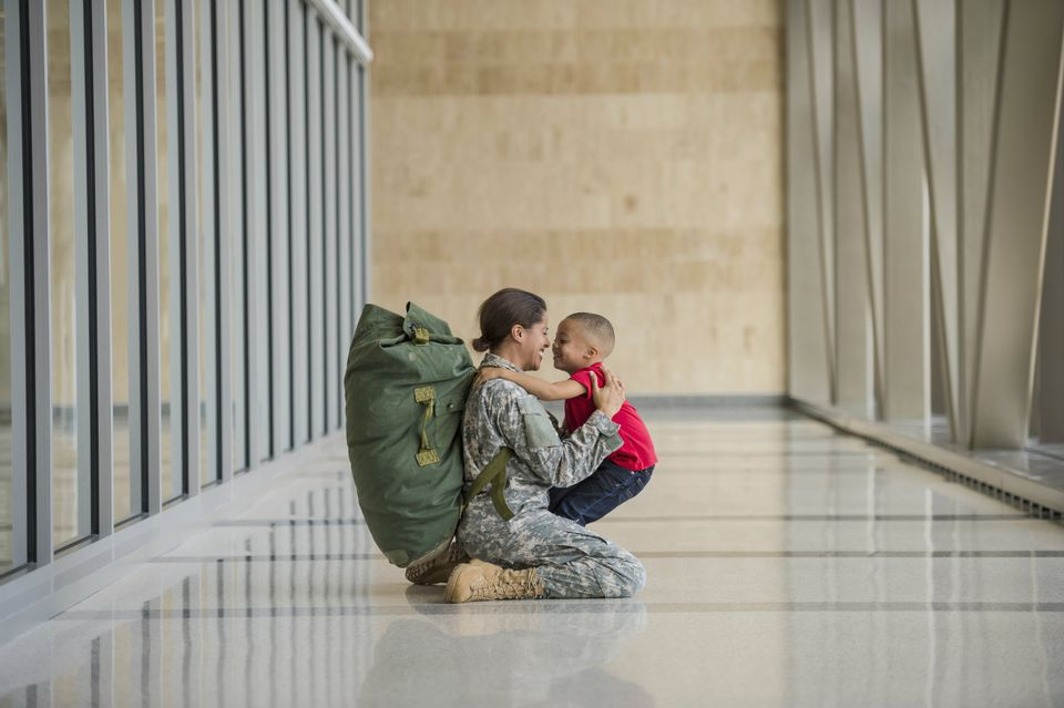 Vet wearing backpack and camo huging child