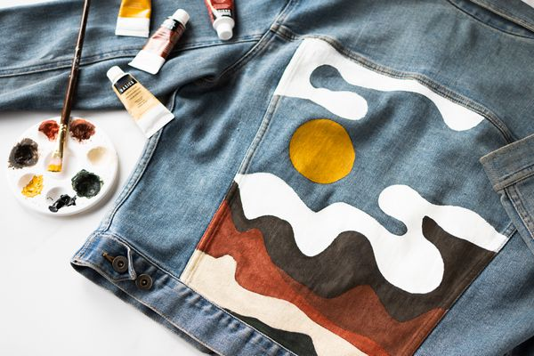 Back of jean jacket with painted scene of landscape next to painting materials