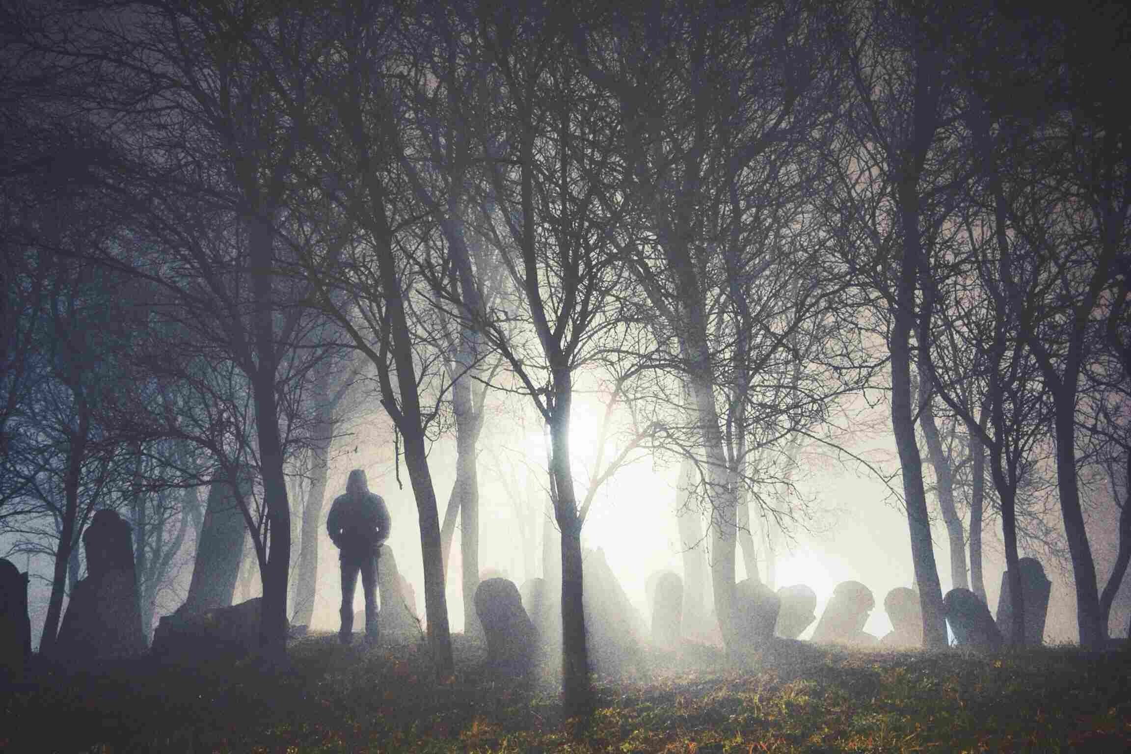 man standing in graveyard