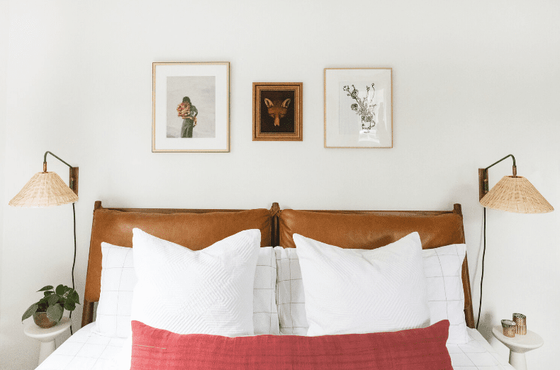 three art pieces above bed with wicker sconces