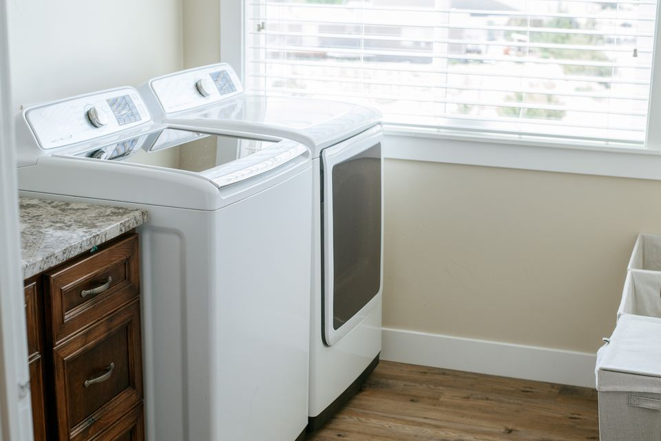 Laundry and dryer machine in tan-colored laundry room by window