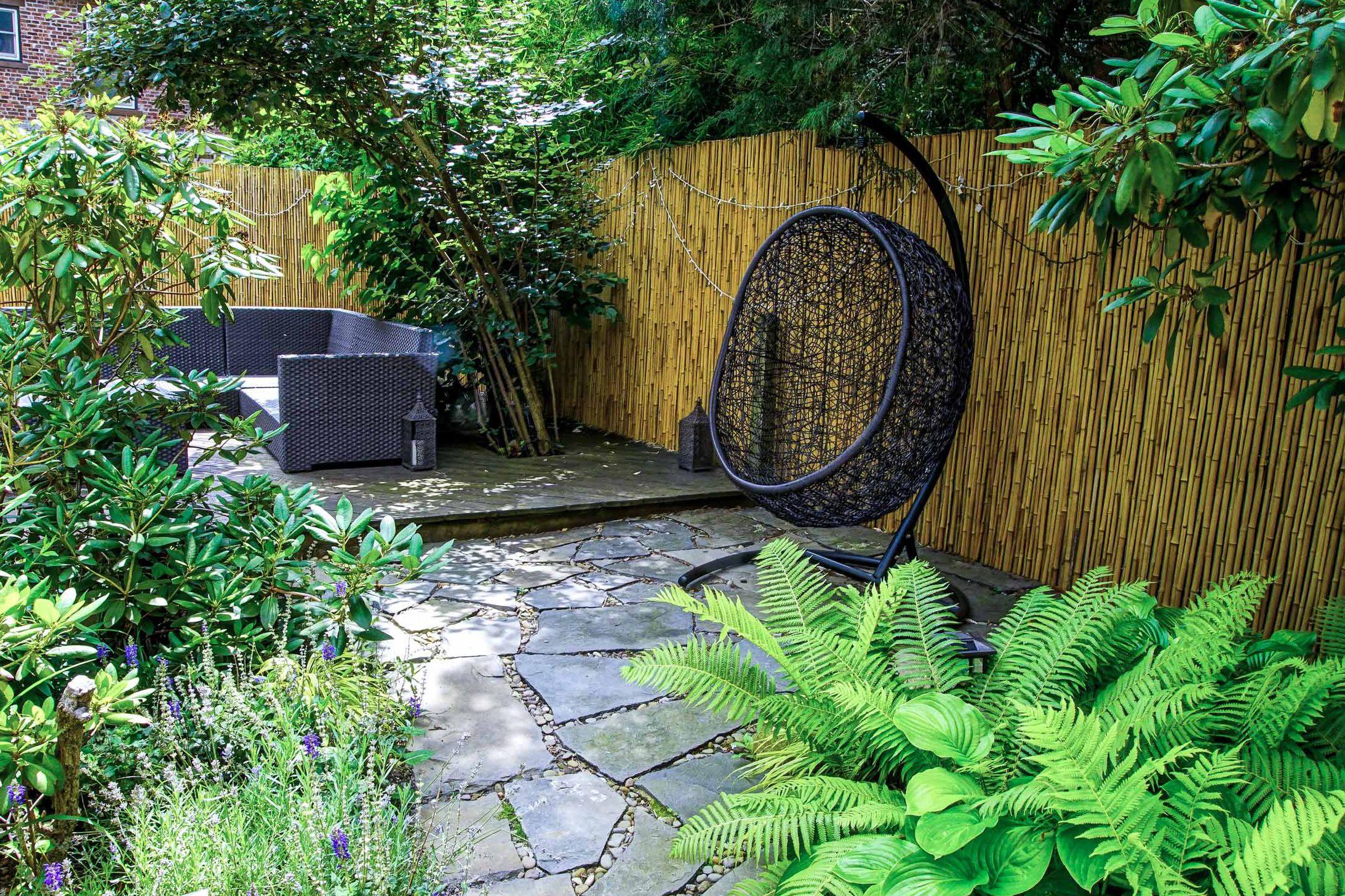 columpio en el patio trasero frente a una pared de bambú