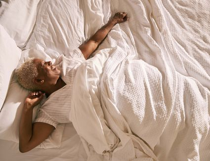 Black woman stretching in all white bed