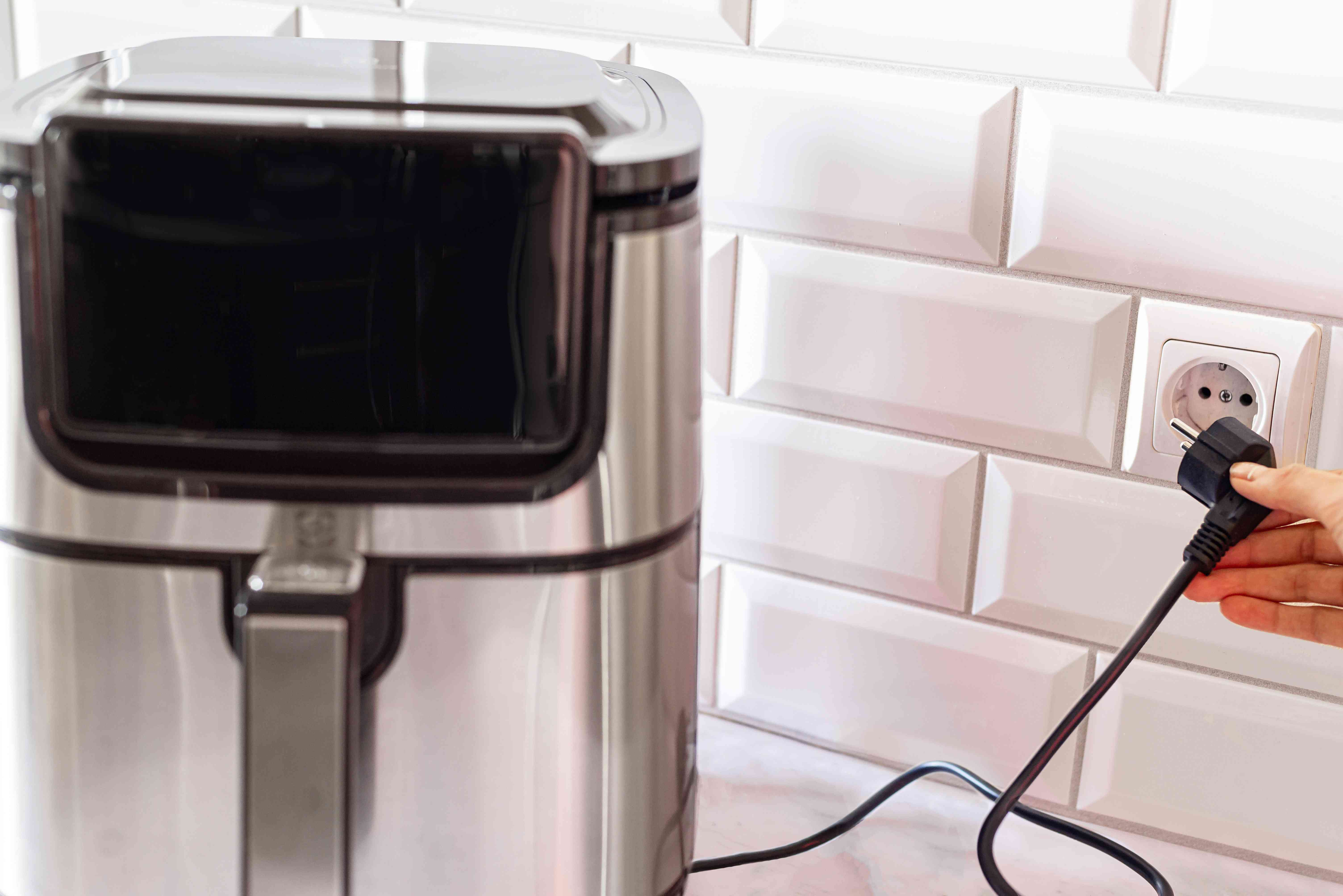 Stainless steel air fryer unplugged from wall to cool