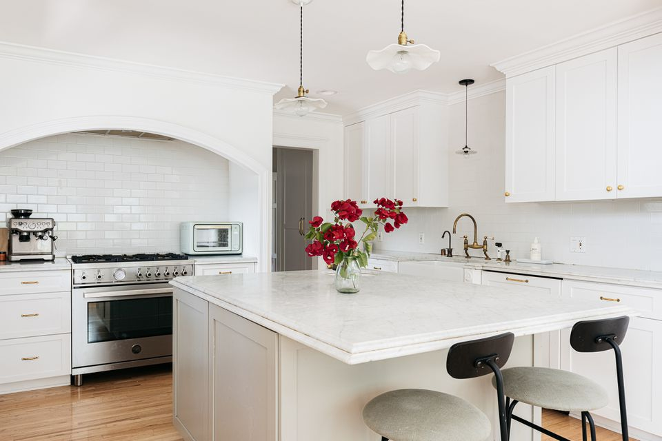 White kitchen cabinets in an all white kitchen with red roses in the middle