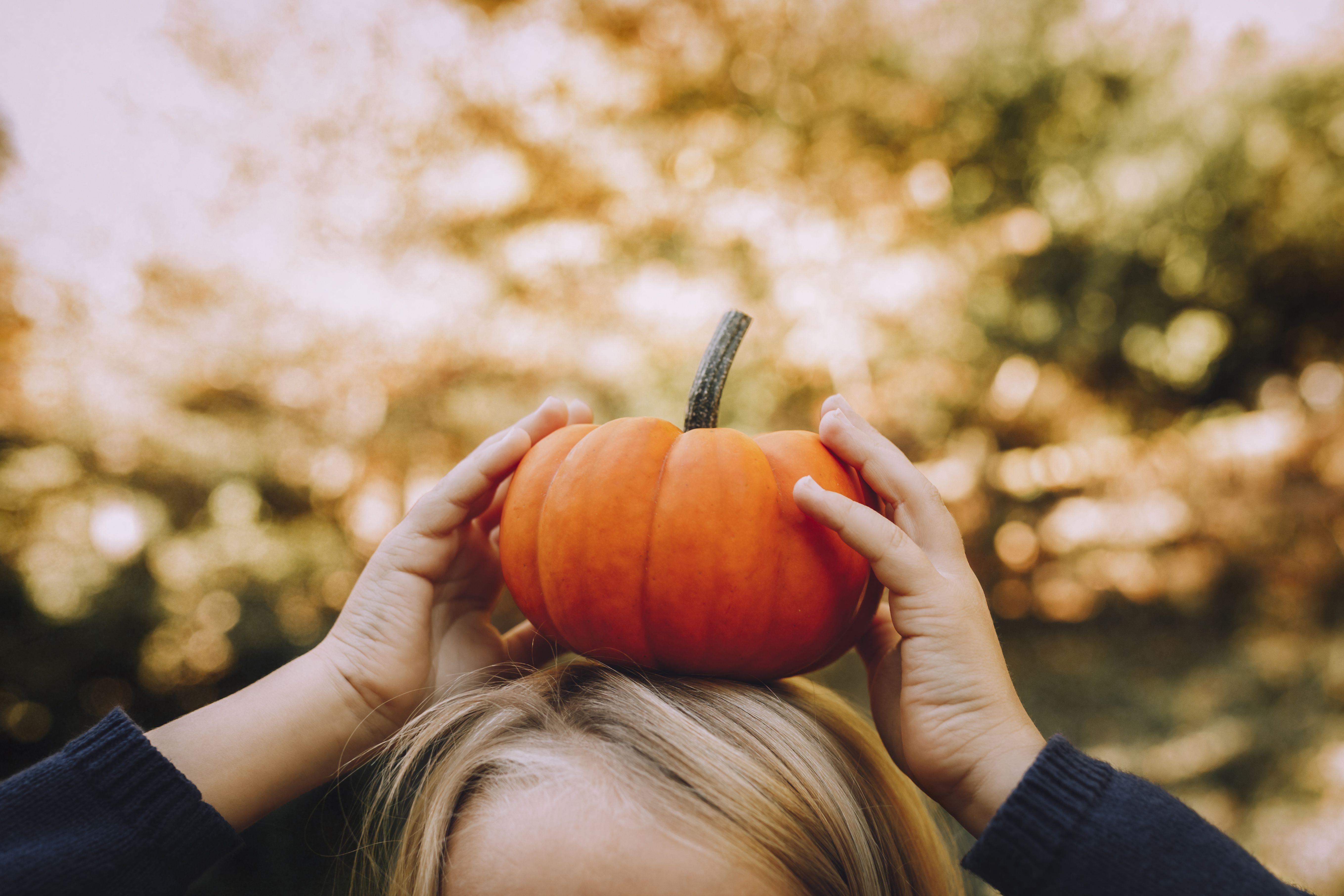 Imagen recortada de una niña equilibrando la calabaza en la cabeza