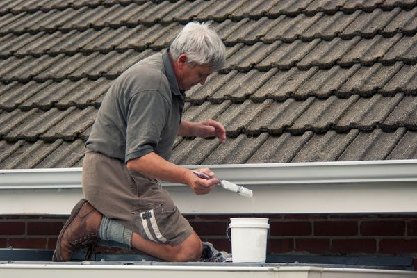 A man painting a roof white