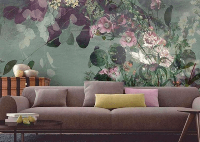 Purple couch in front of floral print wall.