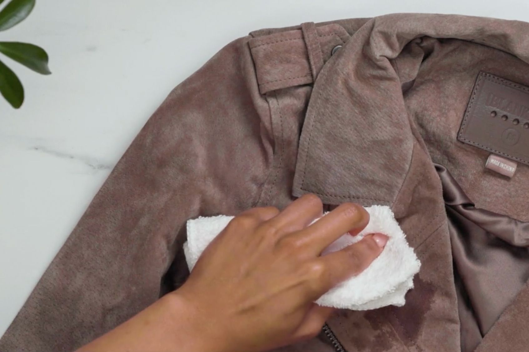 Using a white cloth to brush the suede