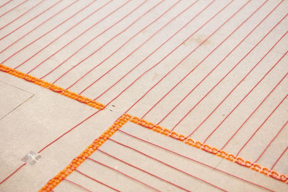 Radiant heat flooring system with orange wires across floor