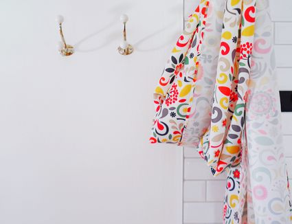 White tiled shower next to white wall with colorful shower curtain bunched up.