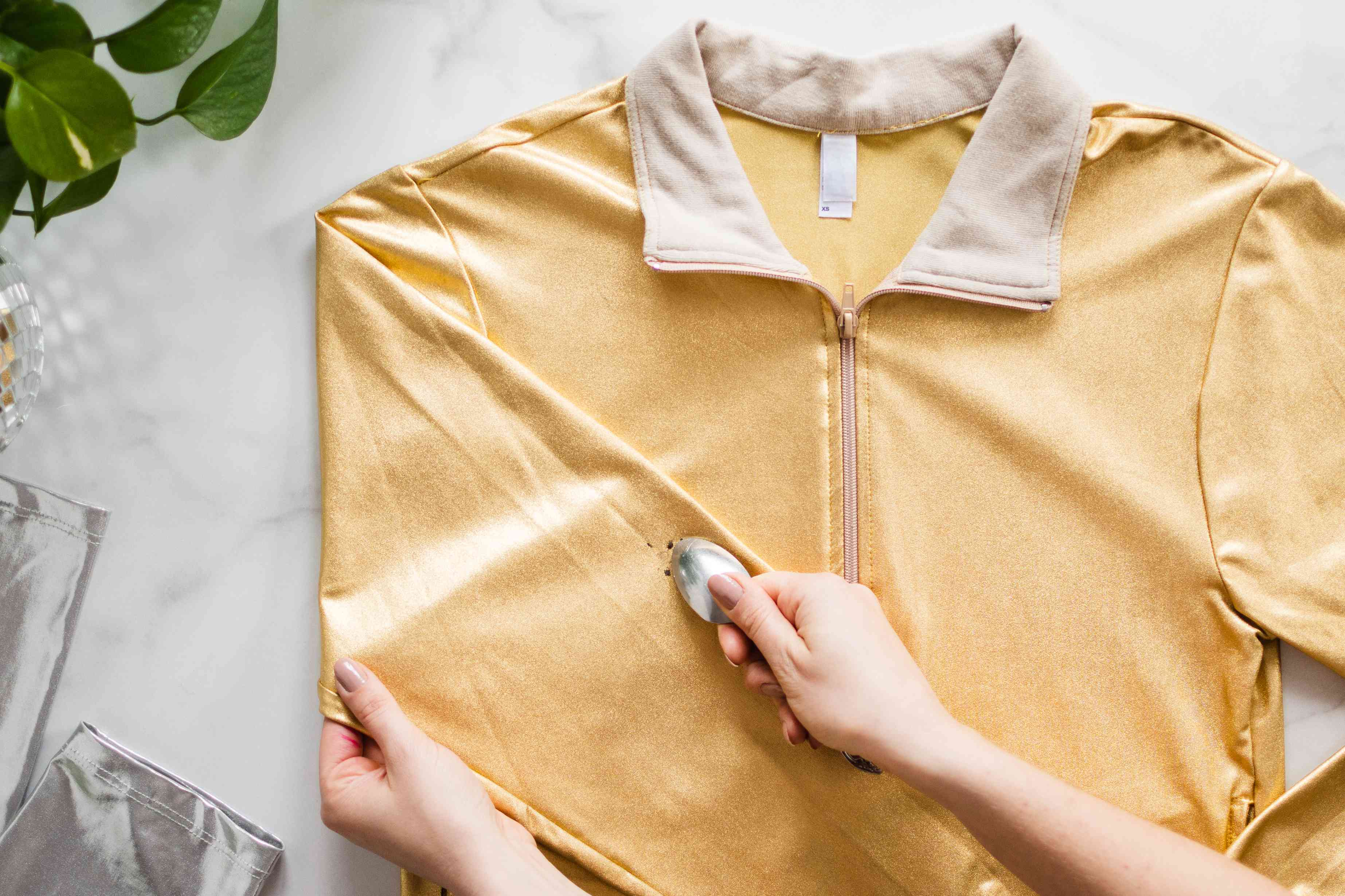 Solid stain residue lifted from left sleeve of yellow metallic jacket