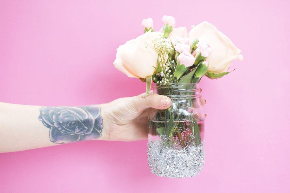 Una mujer sosteniendo un jarrón con flores