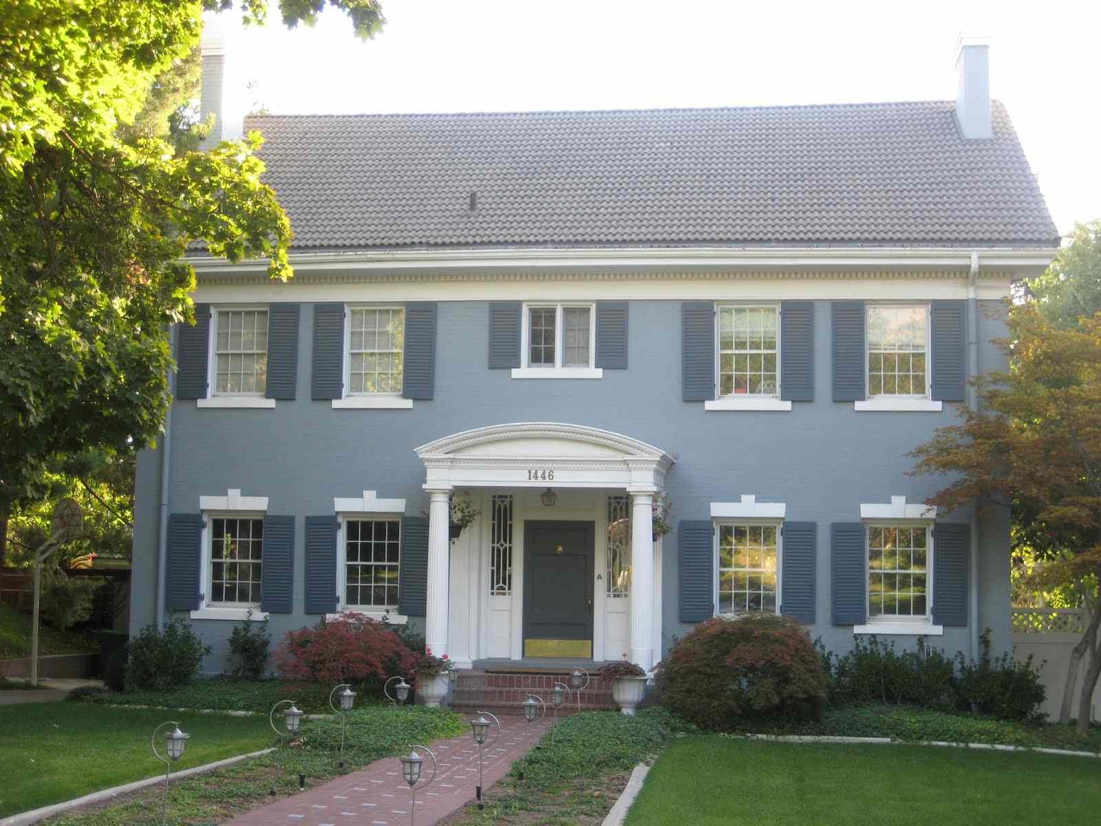Casa de estuco azul con persianas azules