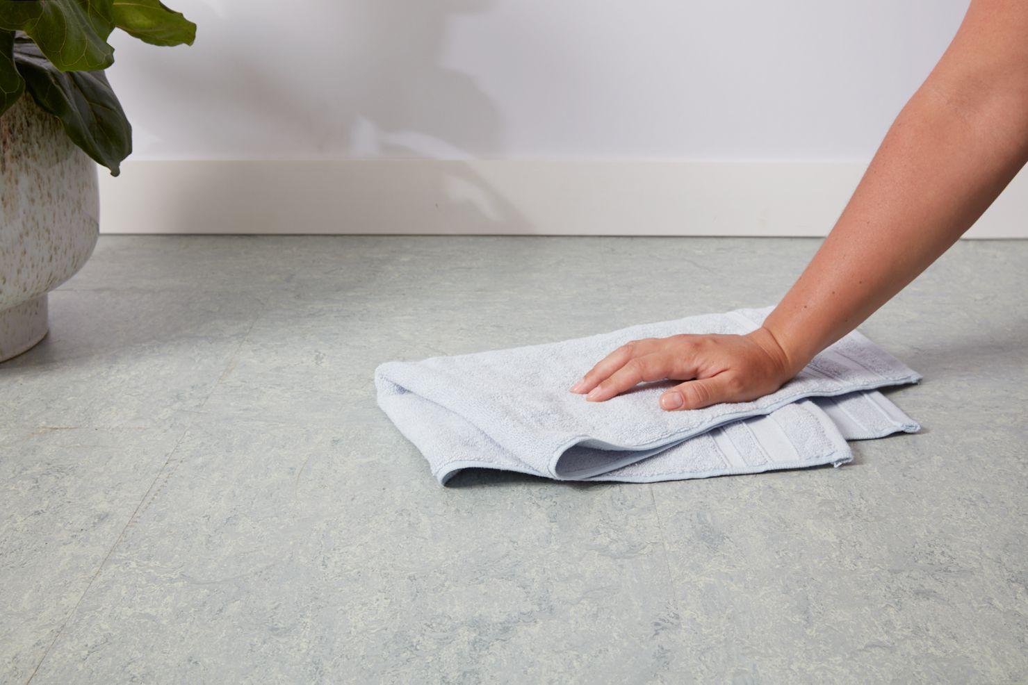 Drying linoleum floor with towel