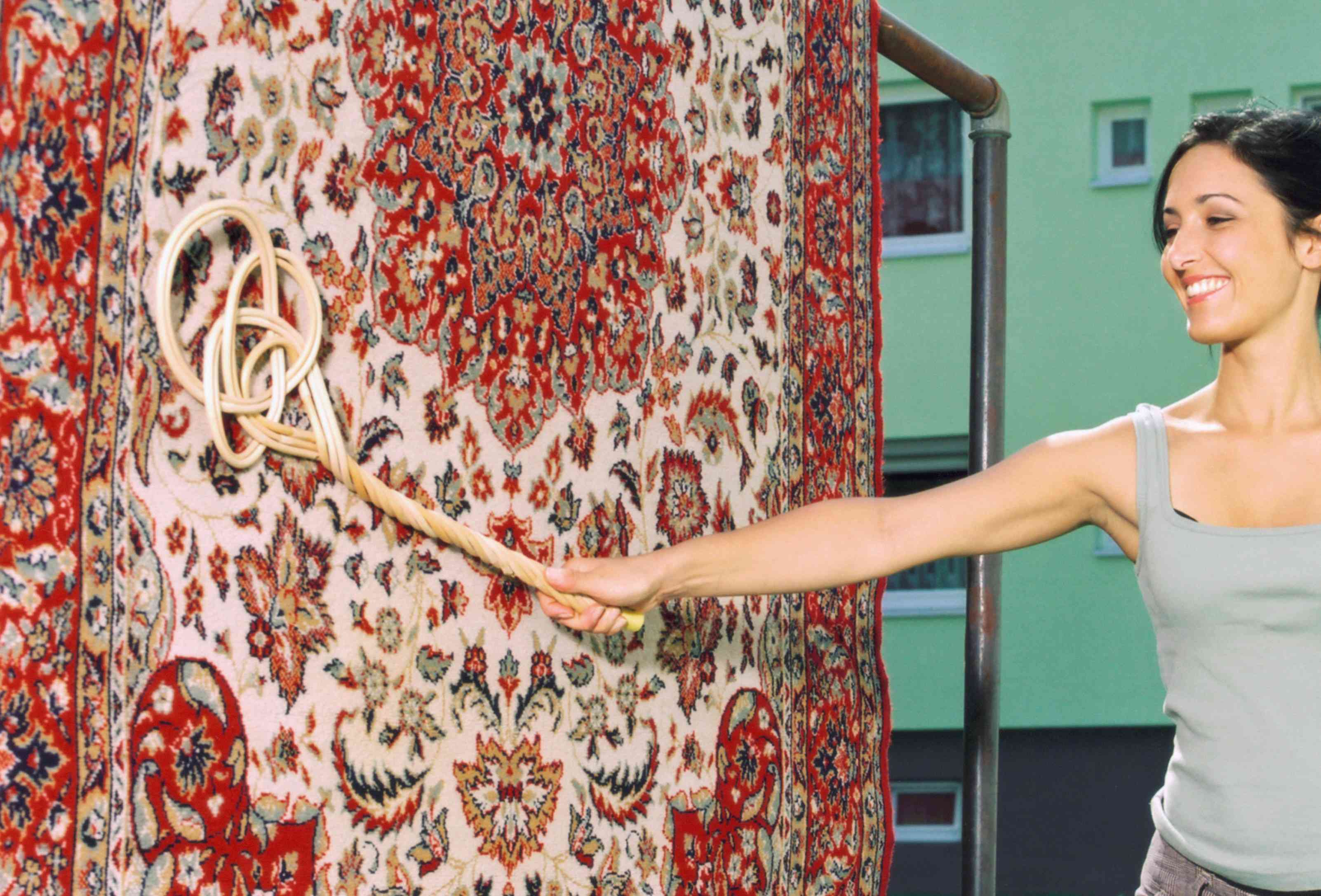 Smiling woman beating carpet with beater